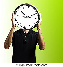 young man with clock - young man covering his face with a...