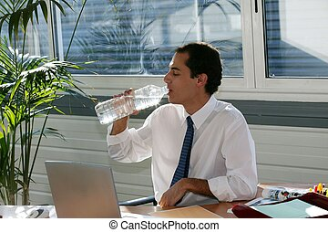 Businessman drinking from a large bottle of water