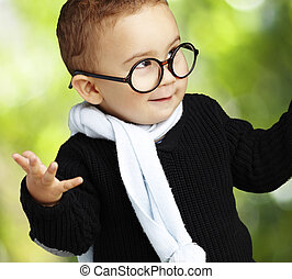 portrait of adorable kid wearing glasses gesturing doubt...