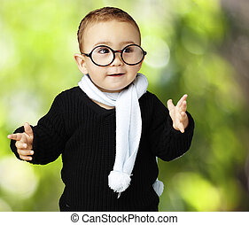 portrait of adorable kid wearing glasses gesturing doubt against