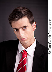 Portrait of a young and sad business man isolated on black background. Studio shot.