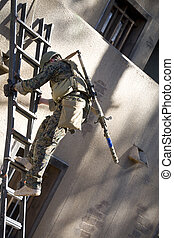 Careful descent - Military marksman going down a ladder with...