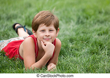 Dreaming boy on the green grass - A dreaming boy is lying on...