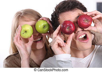 Couple pulling silly faces with apples