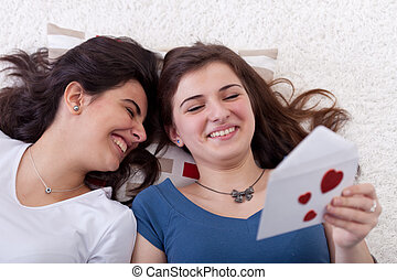 Young teenagers reading love letter and having fun on...