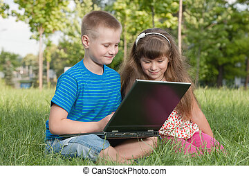 With a laptop on the grass - Two kids are working on a...