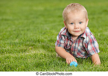 Funny little boy on the green grass - A smiling little boy...