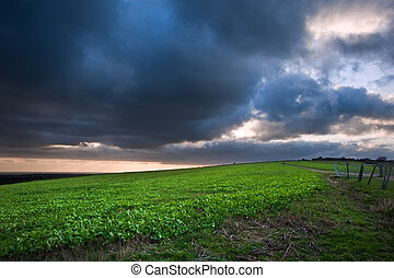 Dramatic cloudy sky over countryside landscape with vibrant colors