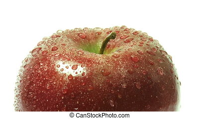 Rotating apple with drops of water closeup