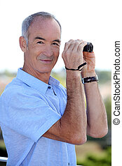 Older man with a pair of binoculars