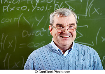 Senior trainee - Portrait of aged teacher looking at camera...