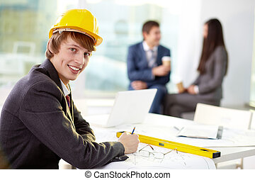 Modern engineer - Young engineer looking at camera with his...