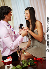 Making proposal - A young man giving engagement ring to his...