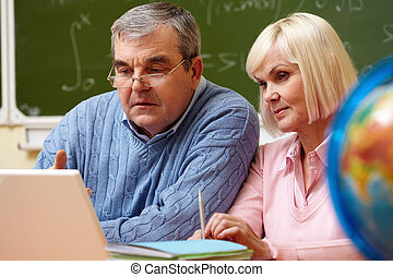 Studying together - Portrait of mature man and aged female...