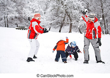 Snowball fight - Family having snowball fight in snowy...