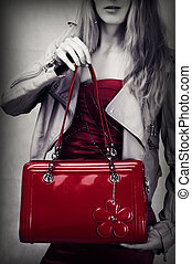 Fashion shot of red patent leather bag in woman hands