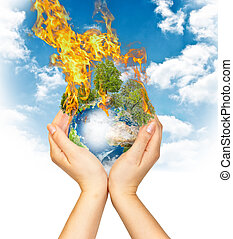 Womanish hands holding burning Earth as a symbol of global...