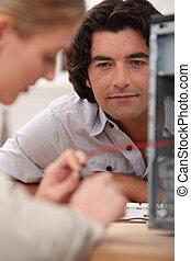 Man watching a woman repairing a television set