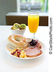 delicious breakfast include egg, orange juice, ham and salad