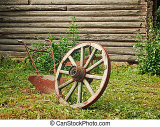 wheel and plough on the grass near the wooden wall