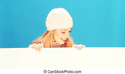 Winter Woman Holding Blank Sign - Smiling blonde woman...