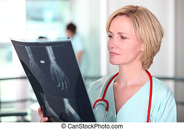 Woman in scrubs examining X-rays