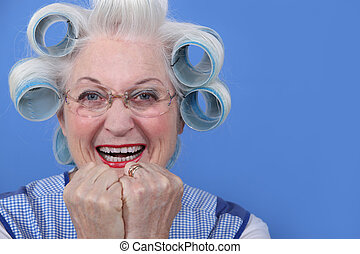 senior woman with curlers in her hair laughing