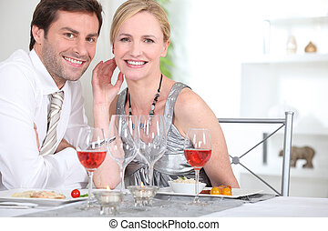 An elegant couple having dinner and smiling at us.