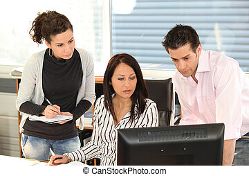 Three colleagues gathered around computer screen