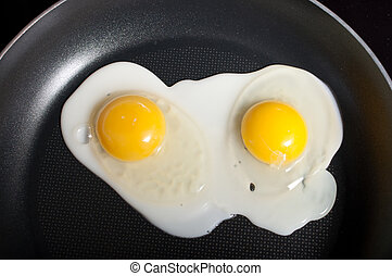 Cooking eggs in a frying pan - Close-up of two frying eggs...