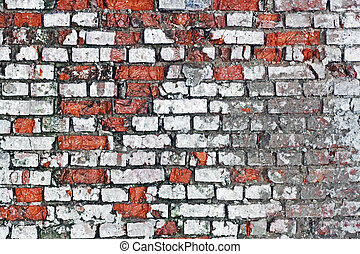 brick wall - An old worn down red brick wall with plaster on...