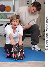 Mature woman sitting on an exercise mat with a personal...