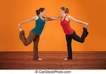 Two Women Perform Yoga - Two Caucasian women perform...