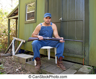 Man with Shotgun guarding his property - Angry looking young...