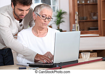 Young man helping a senior with a laptop computer