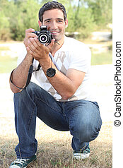 Photographer crouching in the countryside