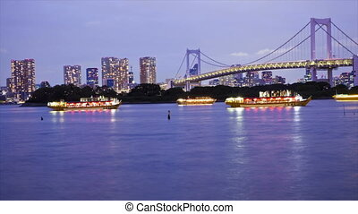 Lighted boats on Tokyo Bay with Tokyo skyline and Rainbow...