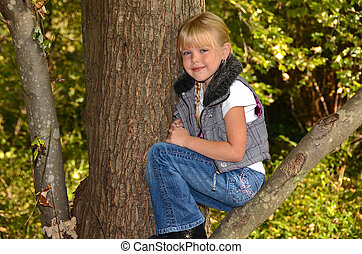 girl sitting in tree - Little blond sitting in an autumn...