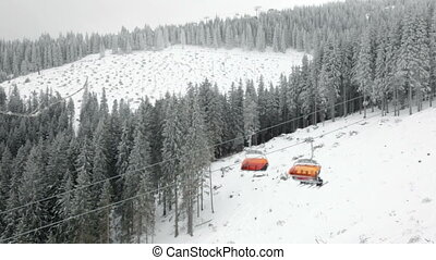 Chairlift in snowy winter mountains - Skiers moving up on a...