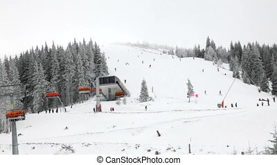 Chairlift station - Skiers and snowboarders going down the...