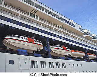 Lifeboats in the side of a big passenger ship...