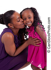 Happy african mother kissing her daughter, isolated on white...