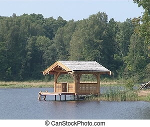 Small wooden summerhouse on lake for recreation. - A small...