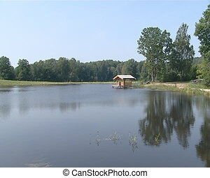 Small wooden summer house on lake for recreation. - A small...