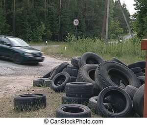 Used tires dumped at roadside. Cars running near.
