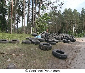 Tires dumped near forest. Nature pollution.