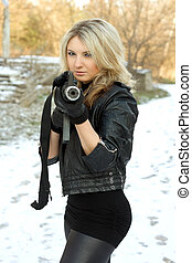 Portrait of nice young blonde with a gun outdoors