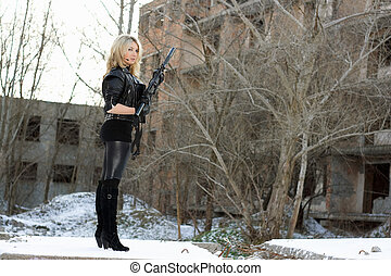 Young sexy woman with a gun outdoors