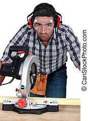 Man with goggles using band-saw