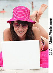 Brunette teenager at the beach with laptop computer